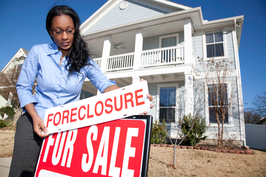 woman placing foreclosure on for sale sign