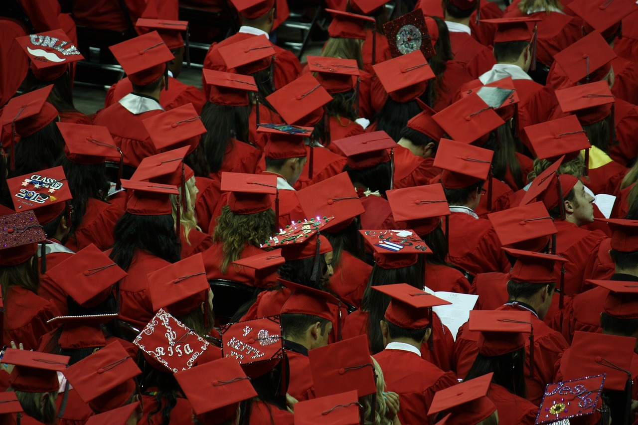 graduates wearing red hats and gowns